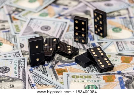 business and finance concept - dominoes and us dollar.