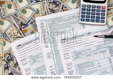 1040 tax from with us dollar banknote pen and calculator.