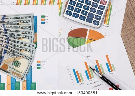 calculator pen dollar banknote above business graph.