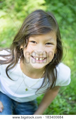Young Pretty Ten Girl Smiling On The Green Grass