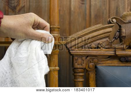 Hand with cloth cleaning wooden parts of antique furniture
