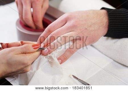 Beautician is doing manicure to her costumer