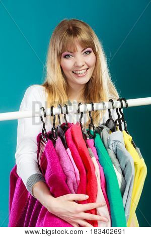 Happy pretty woman grabbing clothing in wardrobe. Young undecided shopper girl takes all from mall shop. Shopaholic concept.