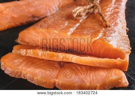 Smoked salmon fish on a slate board. Cutted slices of smoked salmon. Tasty smoked fillet of red fish