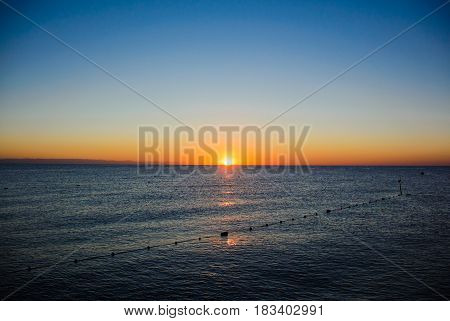 Colourful sea sunrise in soft waves. Summer
