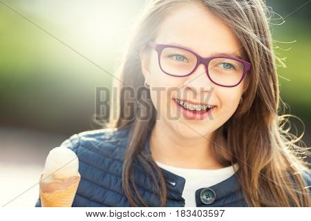 Girl. Teen. Pre teen. Girl with ice cream. Girl with glasses. Girl with teeth braces. Young cute caucasian blond girl wearing teeth braces and glasses. Portrait of a smiling young girl.