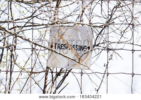 Old and weathered No trespassing sign posted to wire fence safety concept