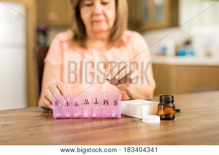 Grandmother Putting Tablets On A Pill Box