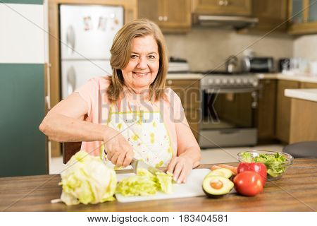 Granny Cutting Lettuce To Add It To A Salad