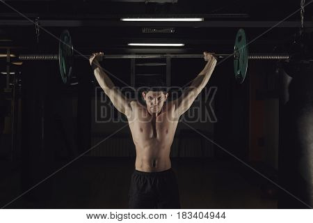 Muscular man at a crossfit gym lifting a barbell