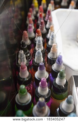 Bottles of colourful tattoo inks in a tattoo parlor box. Closeup