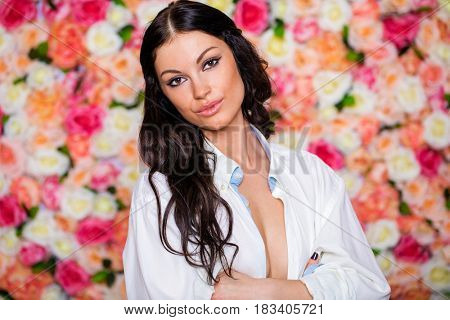 Closeup portrait of a beautiful young brunette woman in a white shirt in a studio on a floral wall background