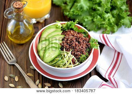 Healthy salad with quinoa, avocado, cucumber and spaghetti from zucchini with lettuce leaf   and olive oil.