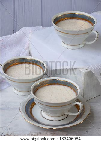 White Dessert Junket From Milk And Rennet Extract With Cinnamon In Cups On Light Background. Jelly-l
