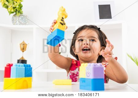cute indian girl child busy playing with toys or blocks, sitting at table