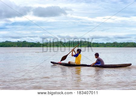 IQUITOS PERU - MARCH 13: Two children navigate the Amazon River in a dugout canoe near Iquitos Peru on March 13 2015
