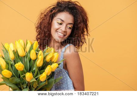 Pleased African woman in blue dress holding bouquet of flowers over yellow background