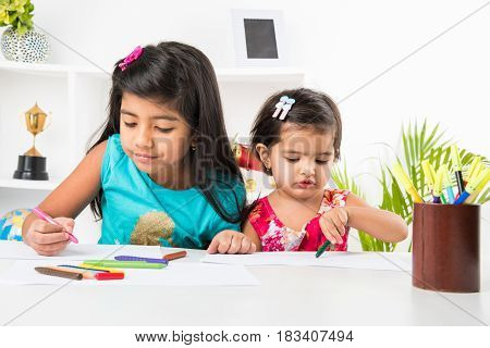 two adorable indian little girls or sisters busy in colouring or drawing or painting using pastel colours or sketch pens at table at home