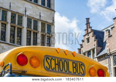 top of a old schoolbus with old school building in the background