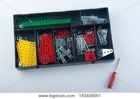 Black plastic box with different colors metal constructor details inside and screwdriver on white background