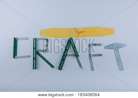 Word craft made of green silver metal constructor details laying on white background