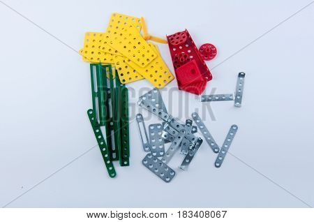 Different size form green yellow red silver metal constructor details with holes laying on white background. Top view