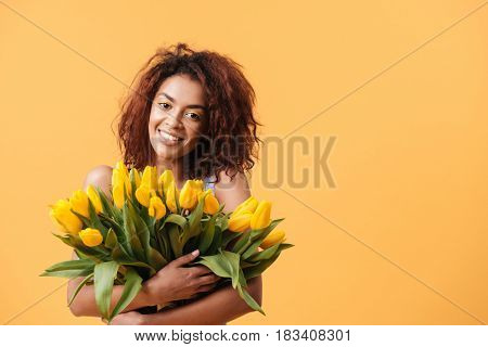 Pleased african woman hugging bouquet of flowers and looking at the camera over yellow background