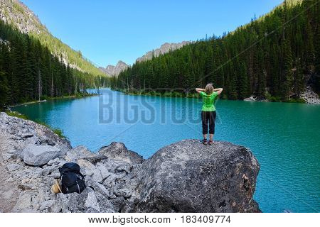 Woman hiker by alpine blue lake. Nada Lake. The Enchantments. Seattle. Leavenworth. WA. United States.