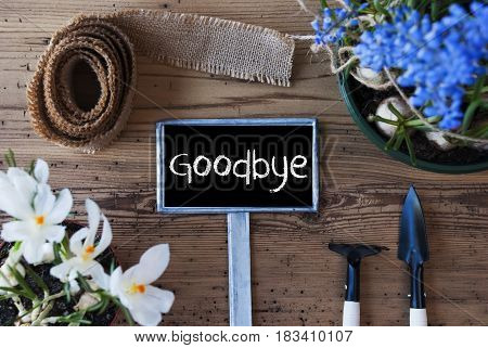 Sign With English Text Goodbye. Spring Flowers Like Grape Hyacinth And Crocus. Gardening Tools Like Rake And Shovel. Hemp Fabric Ribbon. Aged Wooden Background