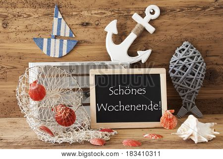 Blackboard With Nautical Summer Decoration And Wooden Background. German Text Schoenes Wochenende Means Happy Weekend. Fish, Anchor, Shells And Fishnet For Maritime Contex.
