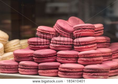 Many pink macaroons or macarons, sweet french cookies. Copy space
