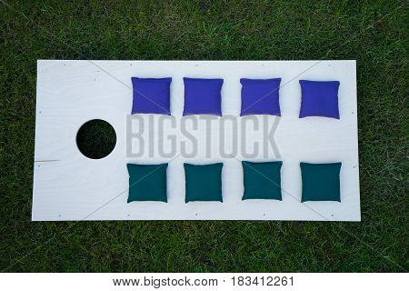 Cornhole Board Flat Lay with beanbags in a row on grass