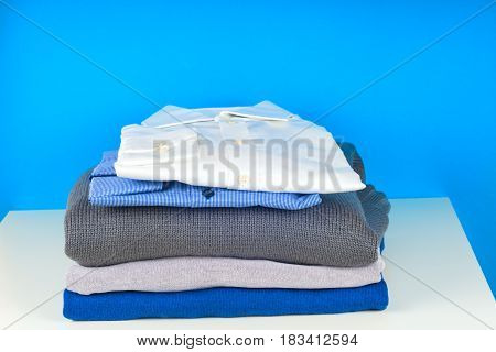 stack of clothing isolated on white sweaters Shirts knitwear space for text