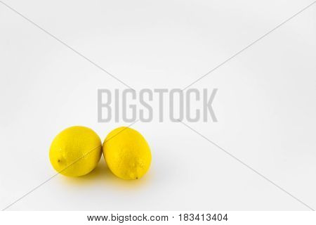 Two whole lemons isolated on white background.