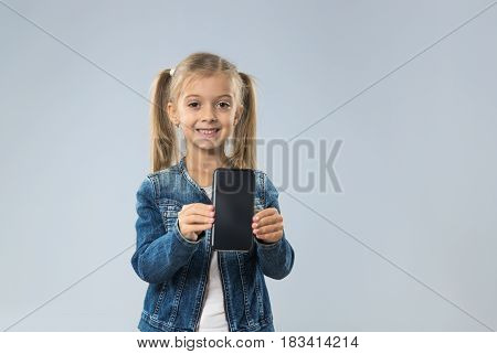 Little Teenage Girl Show Cell Smart Phone Screen With Empty Copy Space, Small Kid Happy Smiling Child Isolated Over Gray Background