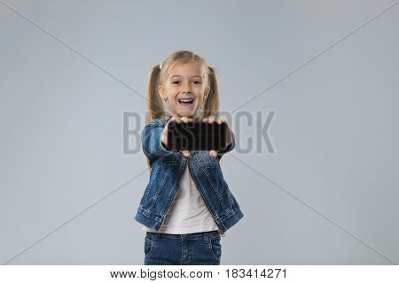 Little Teenage Girl Show Cell Smart Phone Screen With Empty Copy Space, Small Excited Happy Smiling Child Isolated Over Gray Background