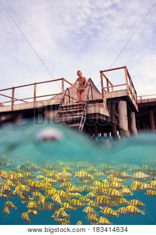 woman on the stairs at descent to the sea and a under water view person is visible through water drops toning