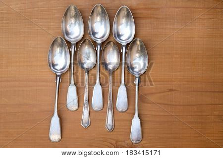 Set of the vintage spoons on wooden background