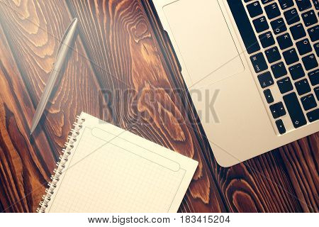 Notepad laptop and pen on wood texture table start of Morning work office vintage style. Business concept background
