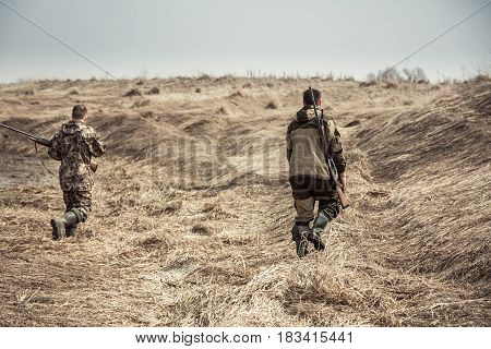 Hunters running across dry rural field during hunting