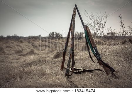 Hunting shotguns in dry rural field in overcast day with dramatic sky during hunting season as hunting background with copy space