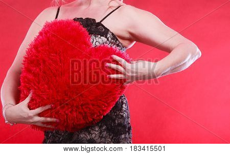 Woman mid aged female wearing black evening dress holding big pillow in form of heart love symbol studio shot on red. Valentines day happiness concept