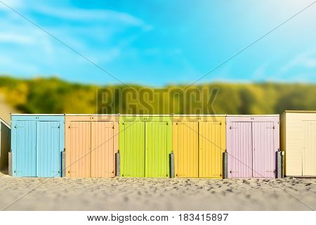 On the Beach by the Sea - beautiful colorful beach huts on a sandy beach on a sunny day - miniature effect - vintage style