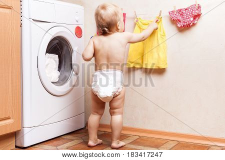 Baby stands near a washing machine and hanging wash clothes