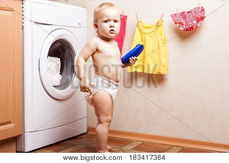 Little girl stands near a washing machine and holding a toy phone