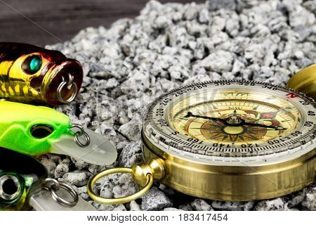 fishing tackles with compass on the sand