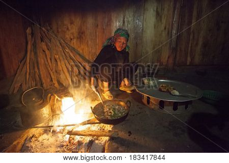 Sa Pa, Vietnam - 14 March, 2017: Ethnic minority, Hmong woman cooking in traditional kitchen in house of Hmong tribal village near Sapa, Vienam