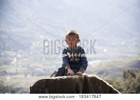 Sa Pa, Vietnam - 14 March, 2017: Unidentified ethnic Hmong minority boy playing on rice terraces in the rural area of Sa Pa, Northern Vietnam, near the border with China.