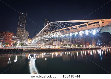 Bilbao cityscape and pedestrian zubizuri bridge at night Bilbao Basque country Spain.