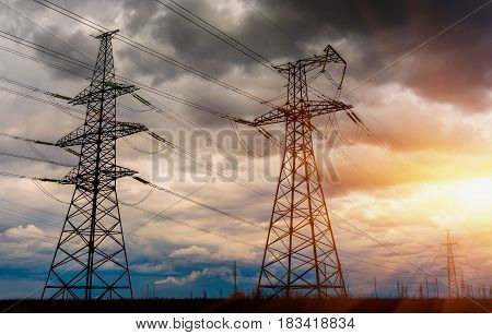 High-voltage lines of electricity transmission are in the field and stormy sky with sun rays